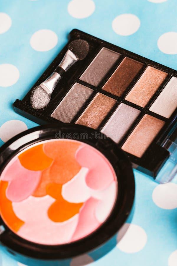 Makeup kosmetyki na błękitnym drewnianym stole i muśnięcie fotografia stock