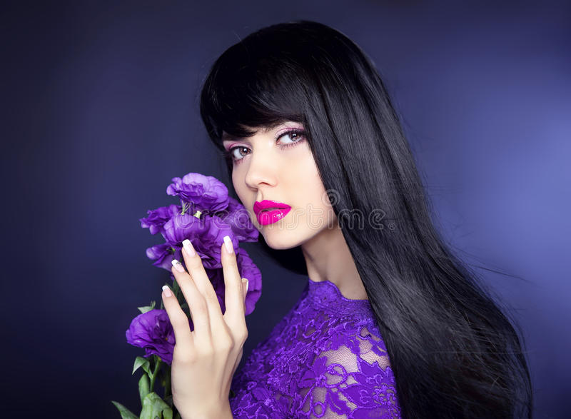 Makeup. Long hair. Beautiful brunette woman with purple flowers, manicured nails, healthy black hairstyle. Beauty studio portrait. royalty free stock image
