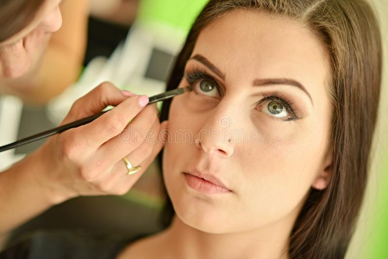 Makeup. Make-up. Eyeshadows. Eye shadow brush. Make-up artist applying bright base color eyeshadow on model's eye royalty free stock photo