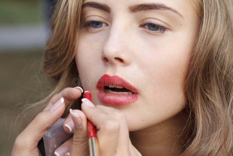 Makeup master paint a beautiful young girl closeup royalty free stock image