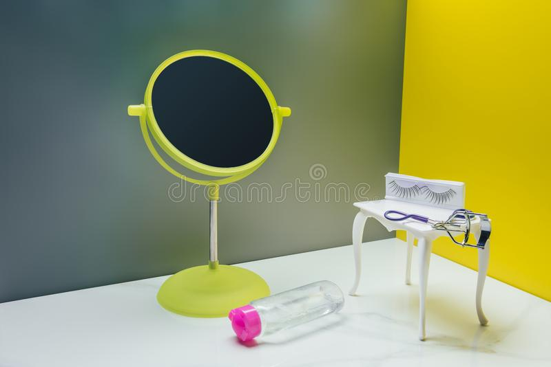 makeup mirror and dressing table with bottle of lotion and eyelash curler royalty free stock photo