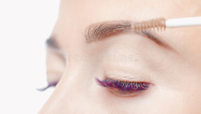 Makeup model process. Permanent makeup eyebrows for young woman in beauty salon, process of applying pigment royalty free stock photo