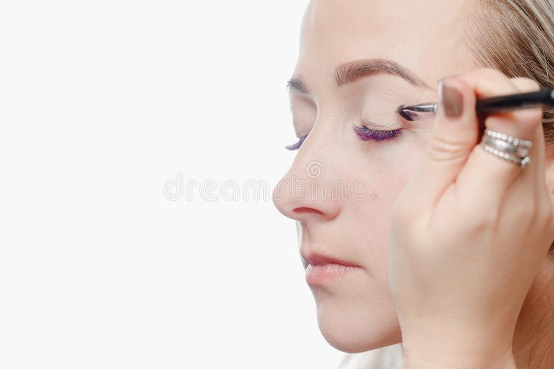 Makeup model process. Permanent makeup eyebrows for young woman in beauty salon, process of applying pigment stock photo