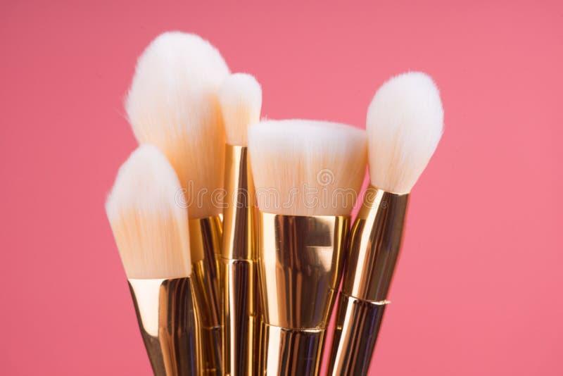 Makeup muśnięcia set na czerwieni menchii pastelu tle obrazy stock