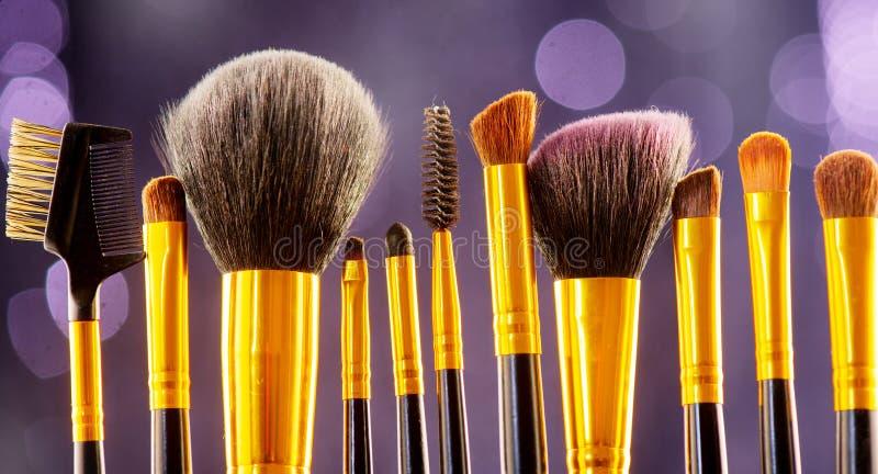 Makeup muśnięcia ustawiają nad czarnym wakacyjnym mrugania tłem Różnorodny profesjonalista uzupełnia muśnięcie na ciemnym tle w s fotografia royalty free