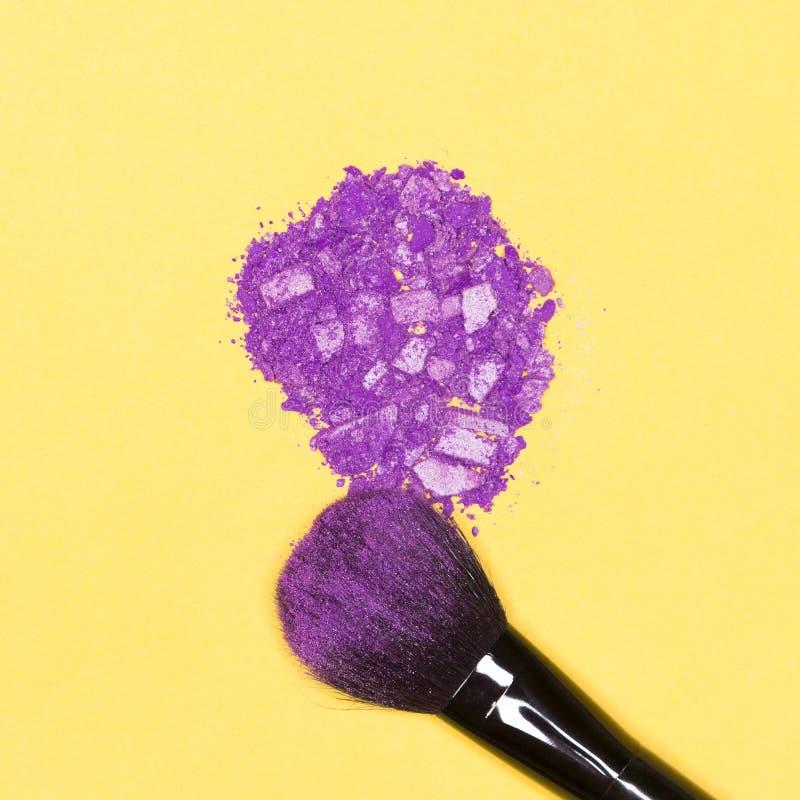 Makeup muśnięcie z pokruszonym fiołkowym oko cieniem na kolorze żółtym zdjęcie stock