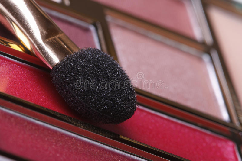 Makeup palette in pink tones with applicator close up. Macro royalty free stock photo