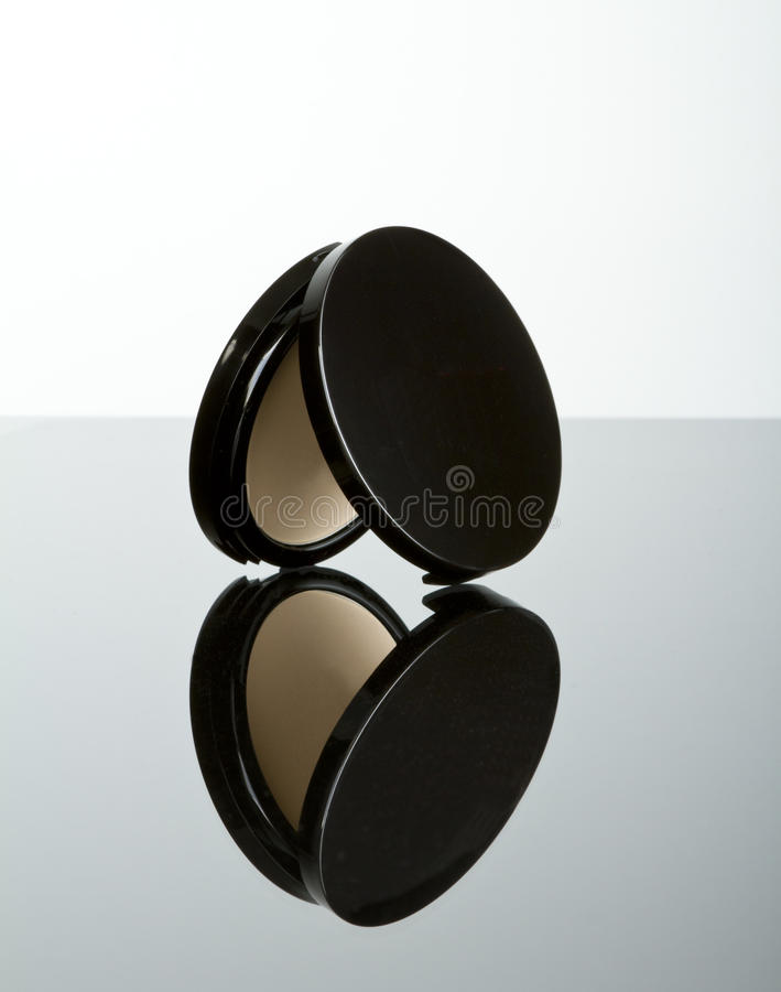 Makeup pressed powder foundation compact. Pressed powder makeup compact with reflection royalty free stock image