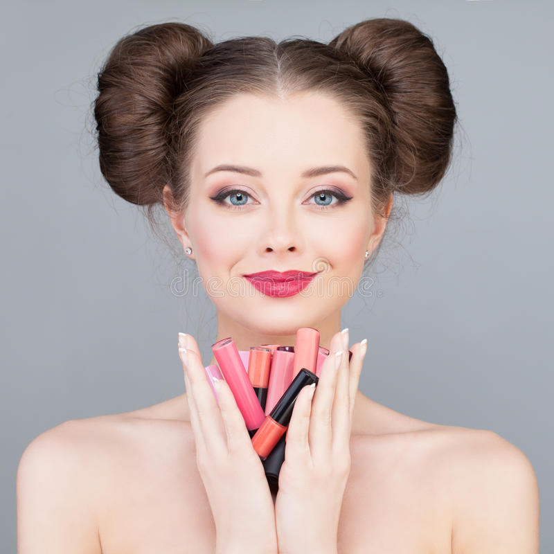 Makeup. Pretty Girl Holding Bright Lipsticks and Lip gloss royalty free stock images