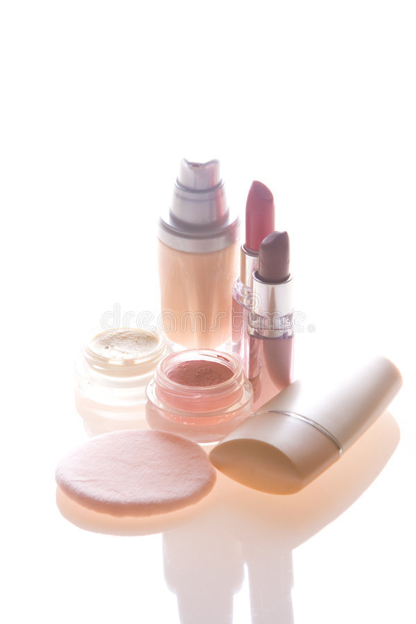 Makeup products. Foundation, lipstick, eyeshadow, blusher and applicator royalty free stock image