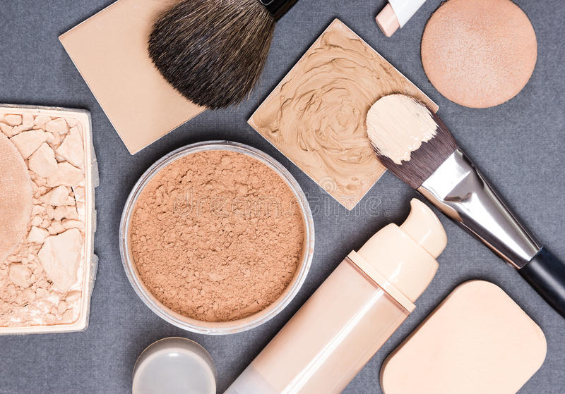 Makeup products and accessories to even out skin tone and comple. Xion on gray textured surface stock image