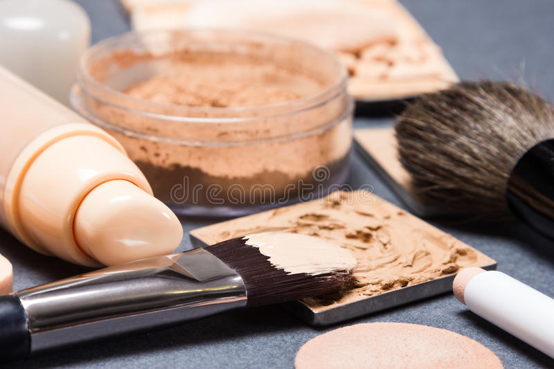 Makeup products and accessories to even out skin tone and comple. Xion on gray textured surface. Side view, very shallow depth of field, focus on bristle of royalty free stock photography