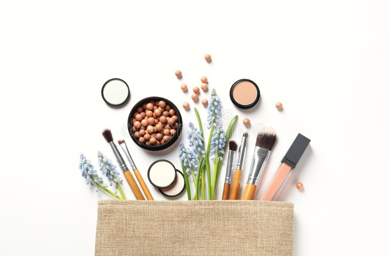 Makeup products and cosmetic bag on white background royalty free stock image