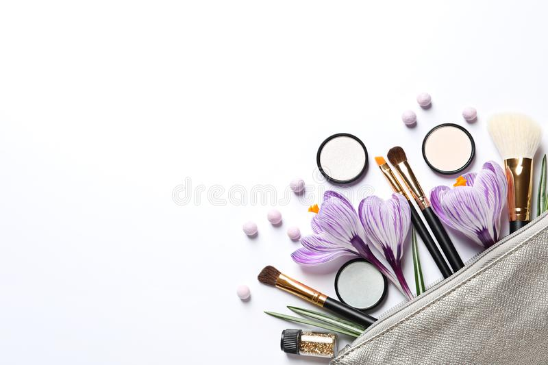 Makeup products, flowers and cosmetic bag, top view royalty free stock photos