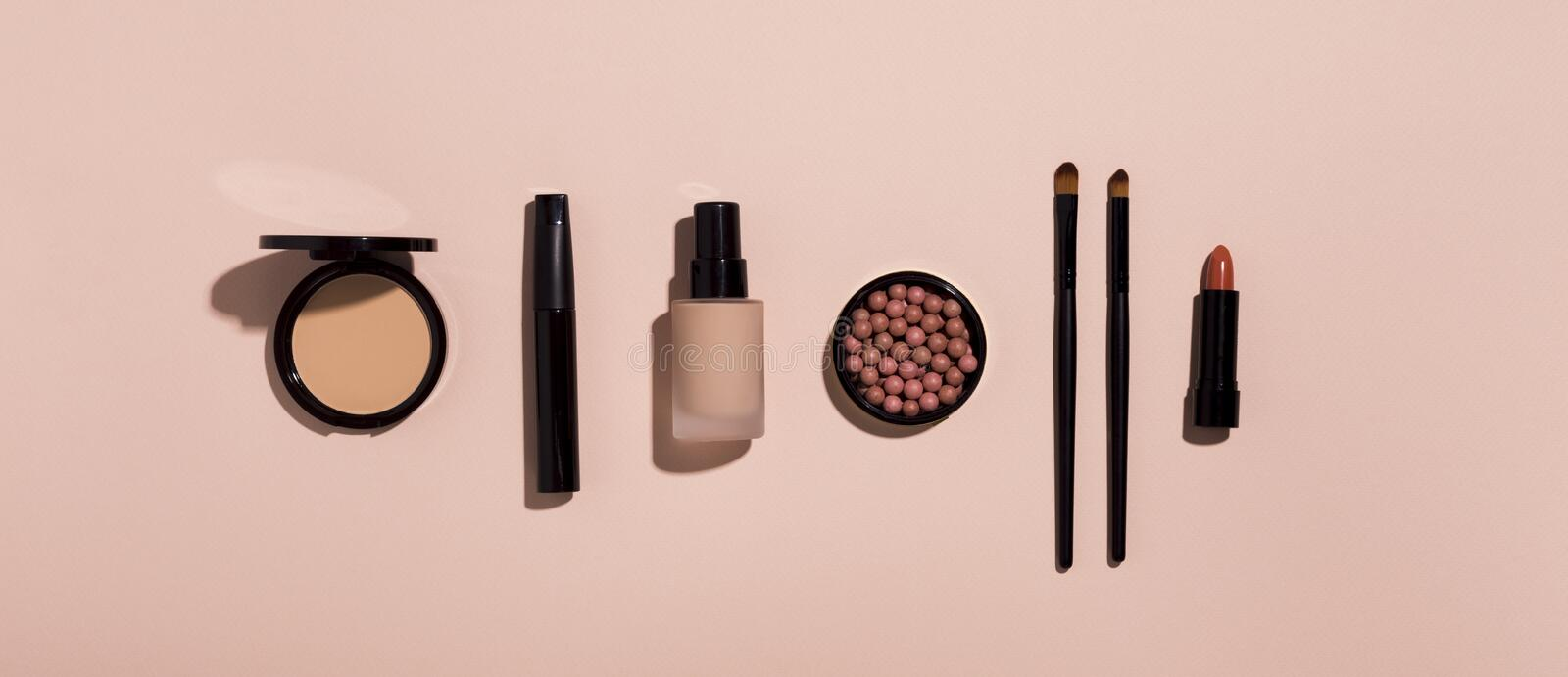 Makeup products in row on pink background stock image