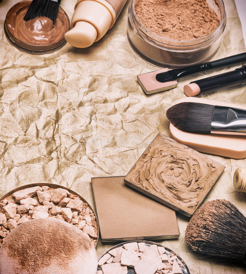 Makeup products to even out skin tone on aged paper frame. Various makeup products to even out skin tone and complexion laid out as semicircular frame on aged royalty free stock photo