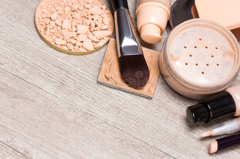 Makeup products to even out skin tone and complexion background. Beauty theme background. Various makeup products and accessories to even out skin tone and stock photography