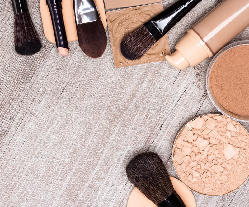 Makeup products to even out skin tone and complexion frame. Makeup products and accessories to even out skin tone and complexion laid out as frame on shabby stock photography