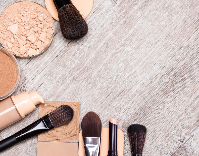 Makeup products to even out skin tone and complexion frame. Makeup products and accessories to even out skin tone and complexion laid out as frame on shabby royalty free stock photo
