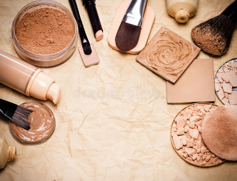 Makeup products to even out skin tone and complexion frame. Various makeup products to even out skin tone and complexion laid out as frame on aged paper. Copy royalty free stock image
