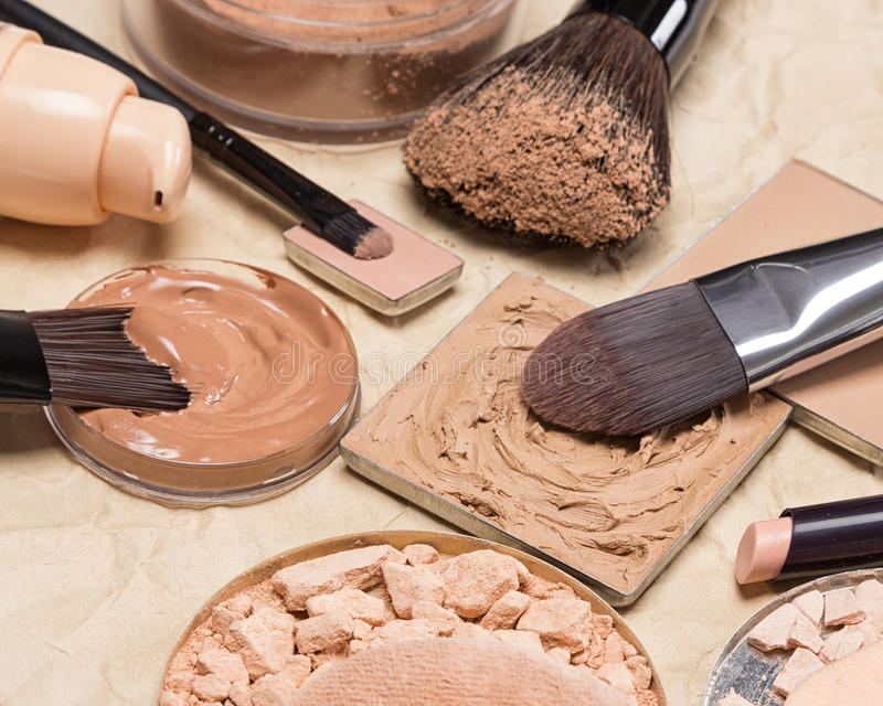 Makeup products to even out skin tone and complexion. Stick concealer, correcting cosmetic powders, cream-to-powder and liquid foundation on crumpled aged paper royalty free stock images