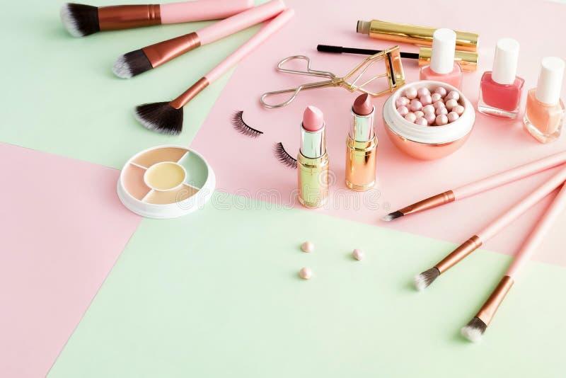 Makeup produkty, dekoracyjni kosmetyki na pastelowego koloru menchii mennicy t?a mieszkaniu nieatutowym obraz royalty free