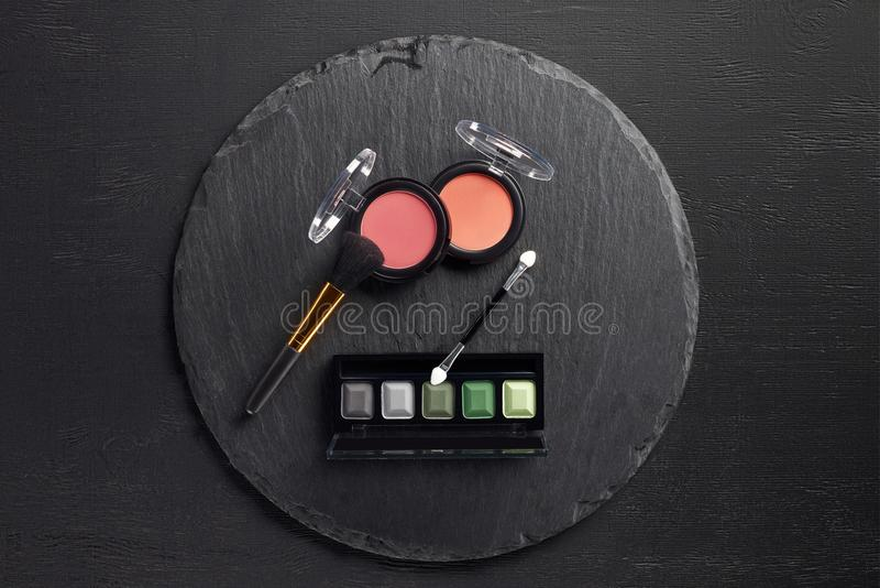 Makeup set with brush, blush and eye shadows on round royalty free stock photos