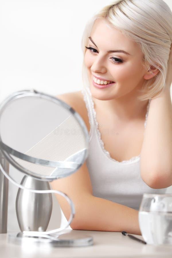 Makeup Stosować. Piękna kobieta Patrzeje Jej twarz w lustrze zdjęcie royalty free