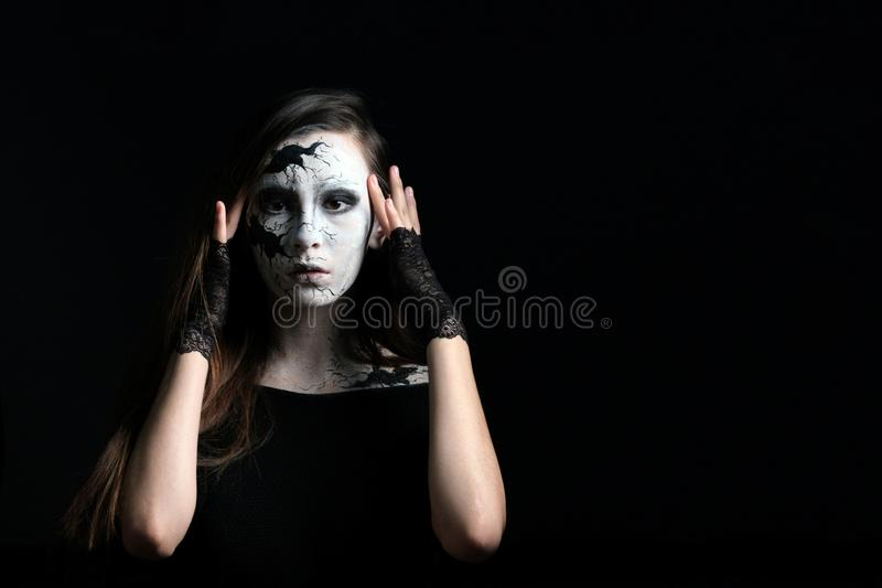 Makeup in the style of Halloween. A young beautiful girl with painted cracks on her face holds fingers of her temples near her eye stock photos