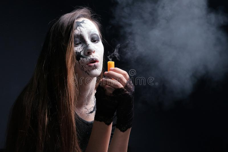 Makeup in the style of Halloween. A young girl with long hair with painted cracks on her face blew out the candle. Dark background royalty free stock image