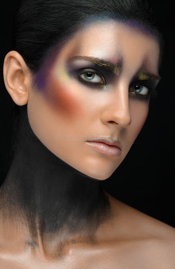 Makeup sztuka i piękny wzorcowy temat: piękna dziewczyna z kreatywnie makijażu złotem i purpurami barwi na czarnym backgroun zdjęcia royalty free