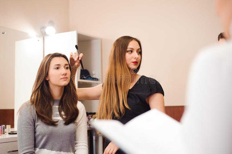 Makeup teacher with her student girls. Makeup tutorial lesson at beauty school. Makeup master class. royalty free stock photography