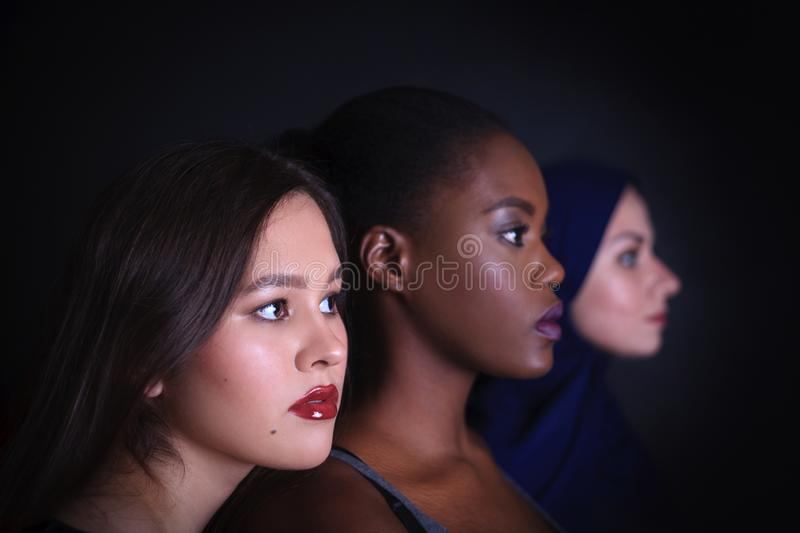 Makeup. Three women portrait. Arabic, asian and afro-american women posing in studio over black background stock photography