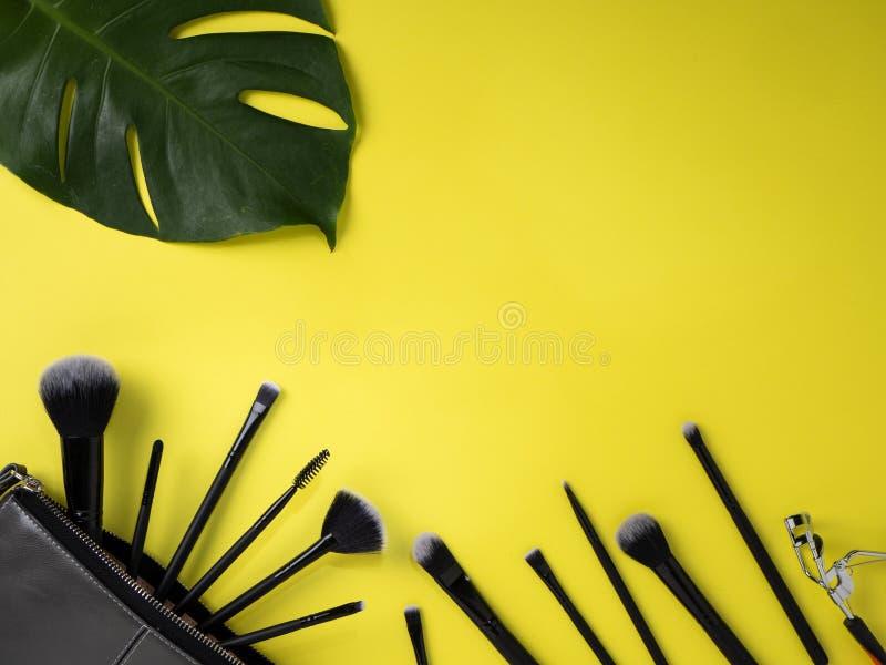 Makeup torba z rozmaitością piękno produktów koloru żółtego tło obrazy stock