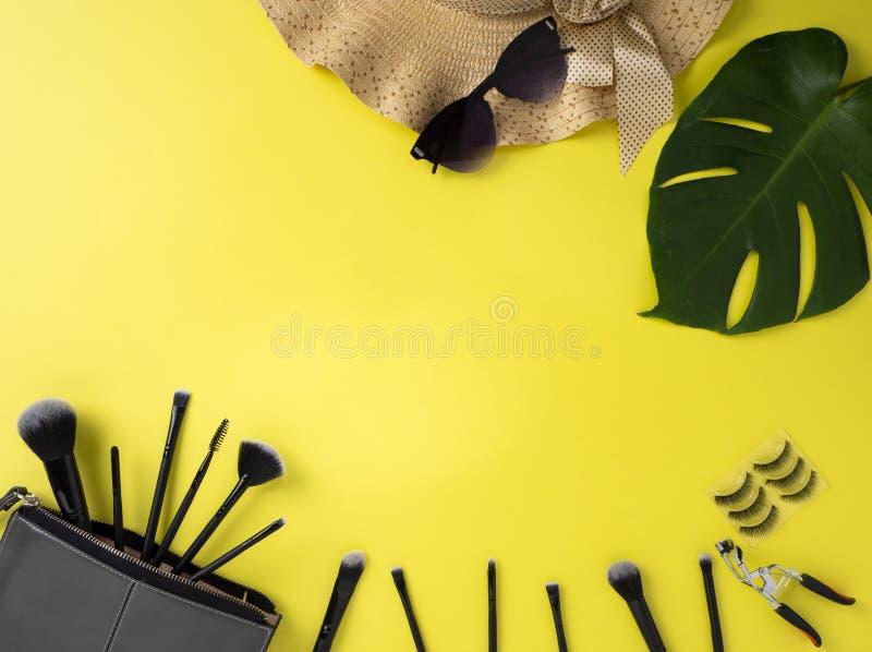 Makeup torba z rozmaitością piękno produktów koloru żółtego tło fotografia stock
