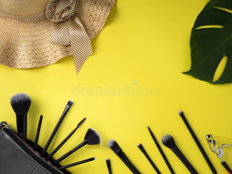 Makeup torba z rozmaitością piękno produktów koloru żółtego tło zdjęcia stock