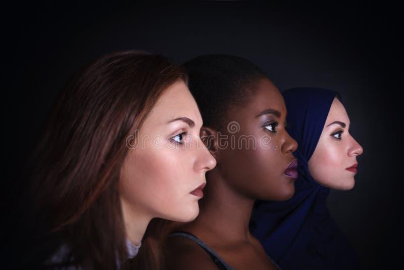 makeup Trzy kobiet portret Kaukaskie i amerykanin kobiety pozuje w studiu nad czarnym tłem fotografia royalty free