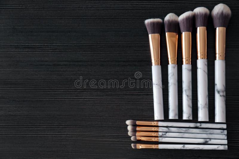 Makeupborstar för att applicera dekorativa skönhetsmedel på mörk träbakgrund arkivbild