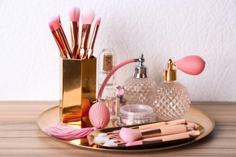 Makeupborstar och dofter på trädressing arkivbild