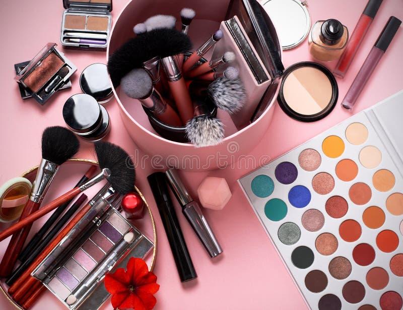 Makeupborstar och skönhetsmedel på en rosa bakgrund, lagringsask arkivfoto