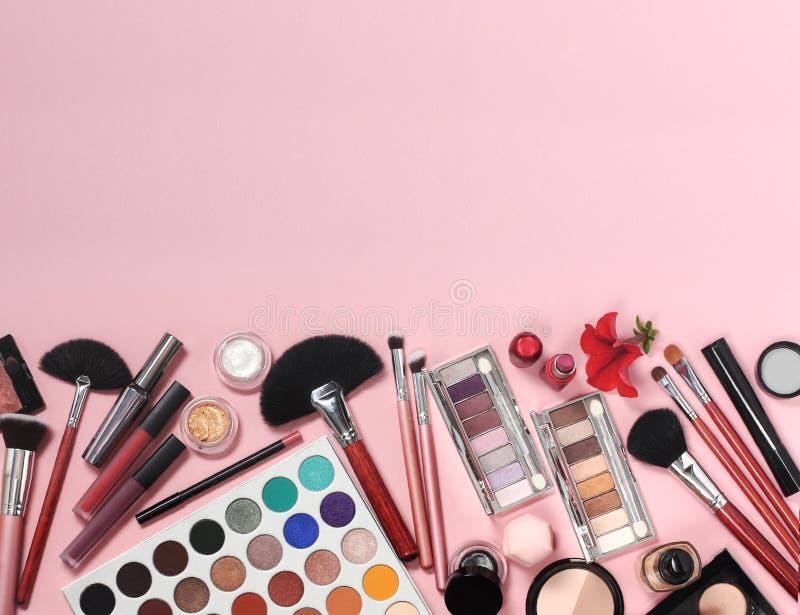 Makeupborstar och skönhetsmedel på en rosa bakgrund royaltyfri bild