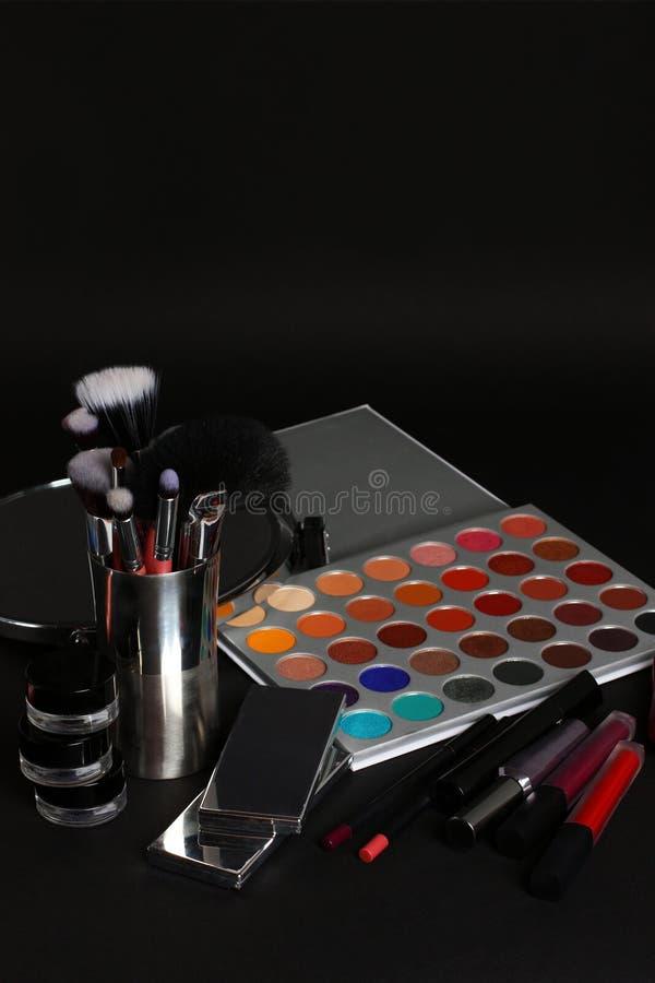 Makeupborstar och skönhetsmedel på en svart bakgrund arkivbild