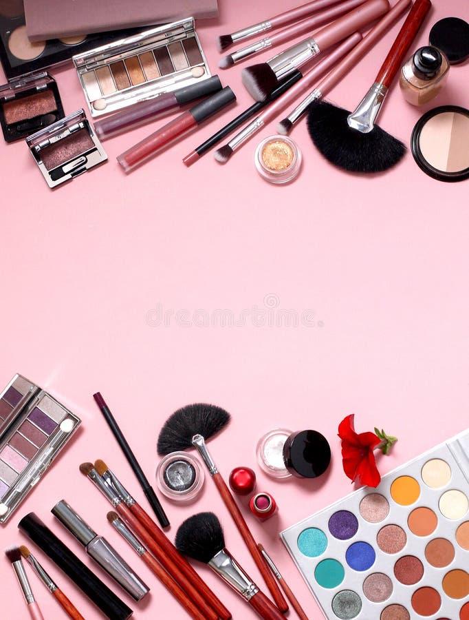 Makeupborstar och sk?nhetsmedel p? en rosa bakgrund royaltyfri bild