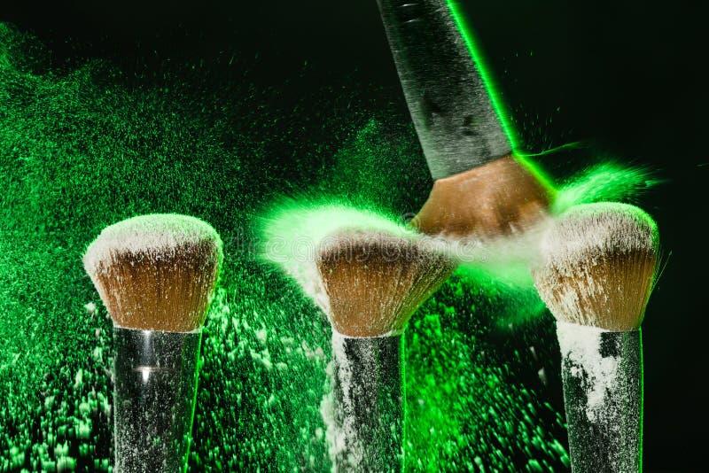Makeupborste med grön mineralisk pulverexplosion på svart bakgrund arkivbild