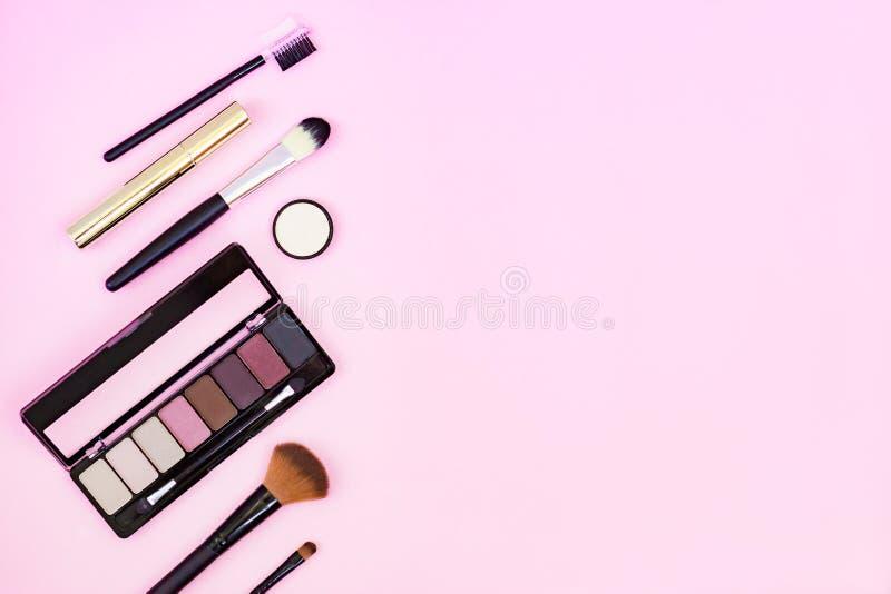 Makeupborste och dekorativa skönhetsmedel på en pastellfärgad rosa bakgrund med tomt utrymme Top besk?dar royaltyfria foton