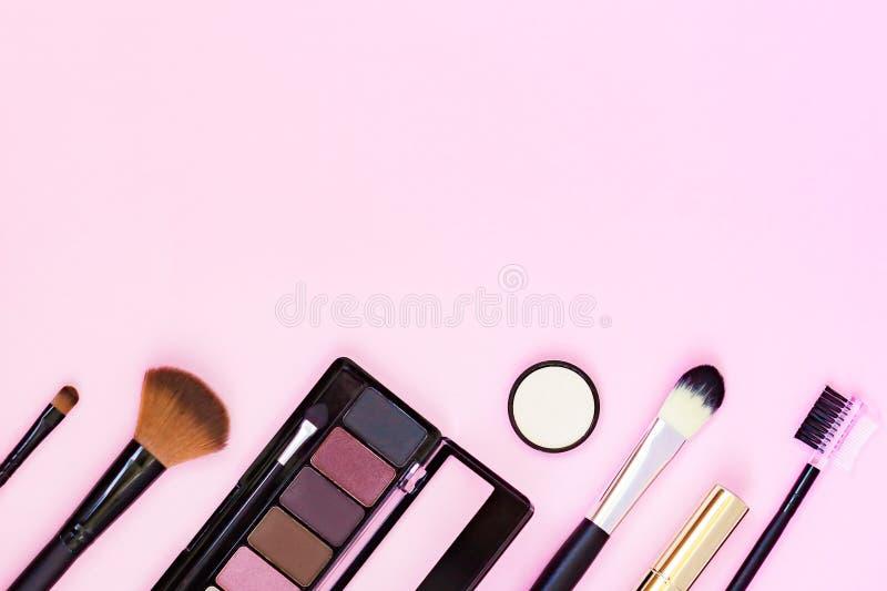 Makeupborste och dekorativa skönhetsmedel på en pastellfärgad rosa bakgrund med tomt utrymme Top besk?dar arkivbilder