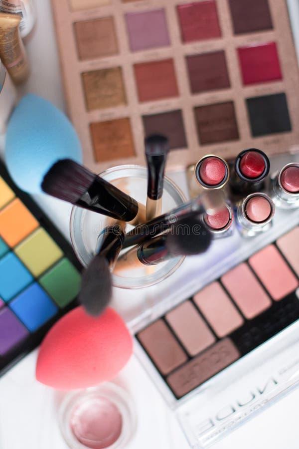 Makeupborste och skönhetsmedel på den vita trätabellen Top beskådar royaltyfri bild