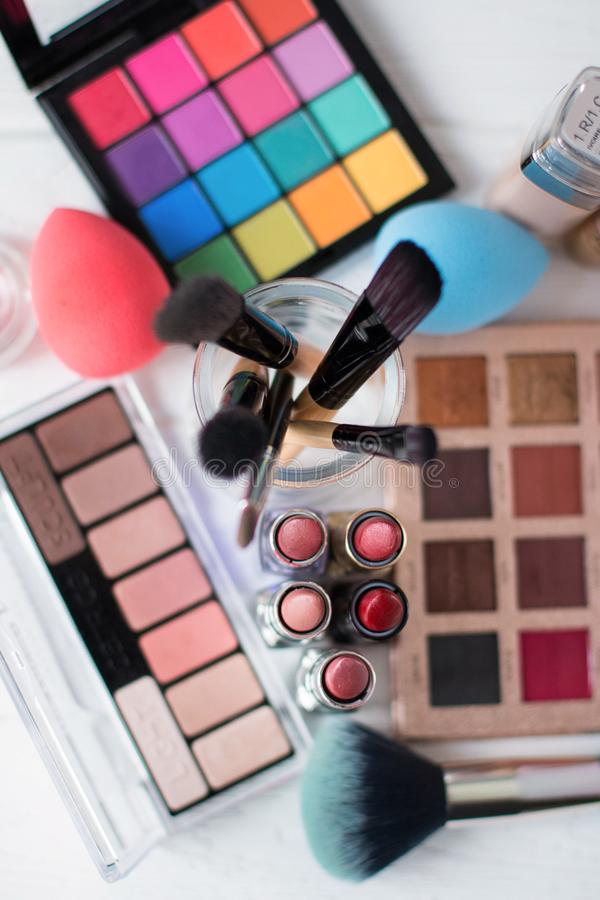 Makeupborste och skönhetsmedel på den vita trätabellen Top beskådar arkivfoto