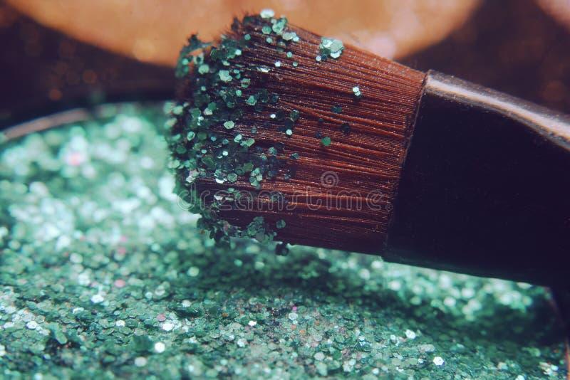 Makeupborste på gröna skinande skuggor Ljusa skuggor med blänker blänker royaltyfria bilder