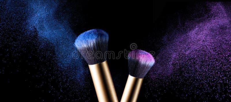 Makeupborsten med rosa färger och blått pudrar explosion arkivbild